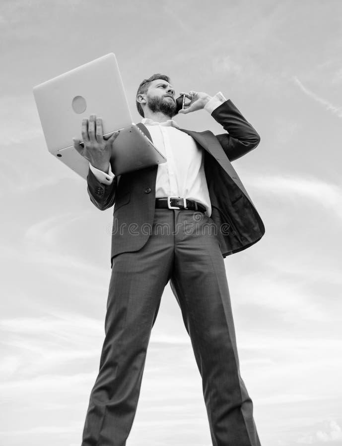 Πάντα στην αφή Ο καλλωπισμένος επιχειρηματίας ατόμων καλά κρατά το lap-top ενώ μιλήστε το υπόβαθρο τηλεφωνικού μπλε ουρανού Επίση στοκ εικόνα
