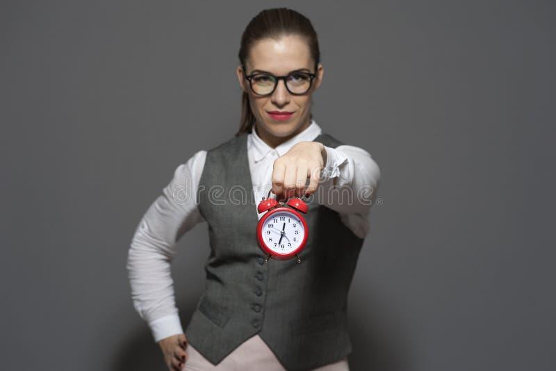 Πάνω στην ώρα έννοια - νέα γυναίκα με το κόκκινο ρολόι στοκ φωτογραφία