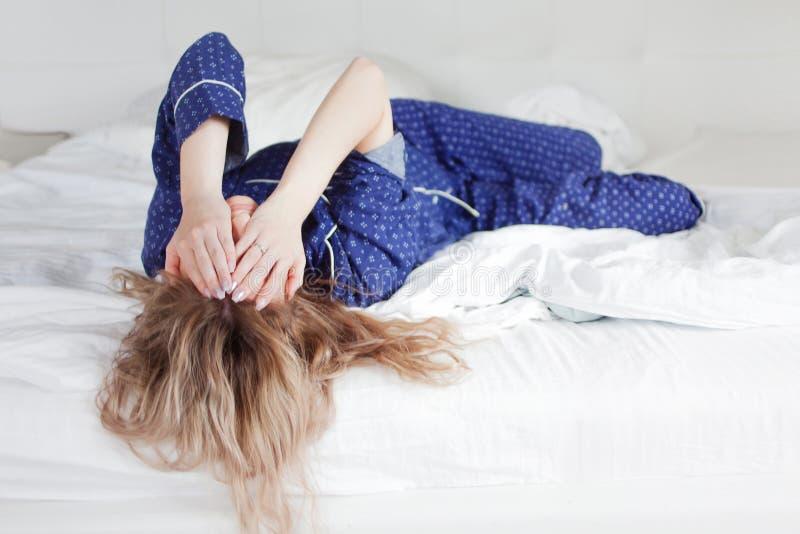 Πάρα πολύ οκνηρός να πάρει από το κρεβάτι, μια γυναίκα που καλύπτει το πρόσωπό της με το χέρι στοκ εικόνα με δικαίωμα ελεύθερης χρήσης