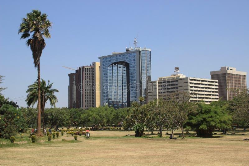 πάρκο κεντρικών πόλεων με τους φοίνικες και την άποψη εμπορικών κέντρων στοκ φωτογραφία με δικαίωμα ελεύθερης χρήσης