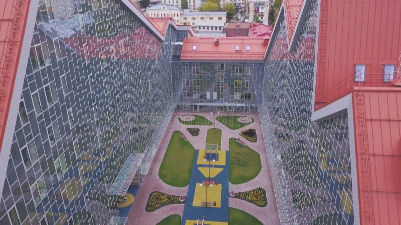 Πάρκο μεταξύ των κτηρίων γυαλιού συνδετήρας Τοπ άποψη της στηργμένος θέσης με το χορτοτάπητα μεταξύ των προσόψεων γυαλιού των κτη στοκ φωτογραφία με δικαίωμα ελεύθερης χρήσης