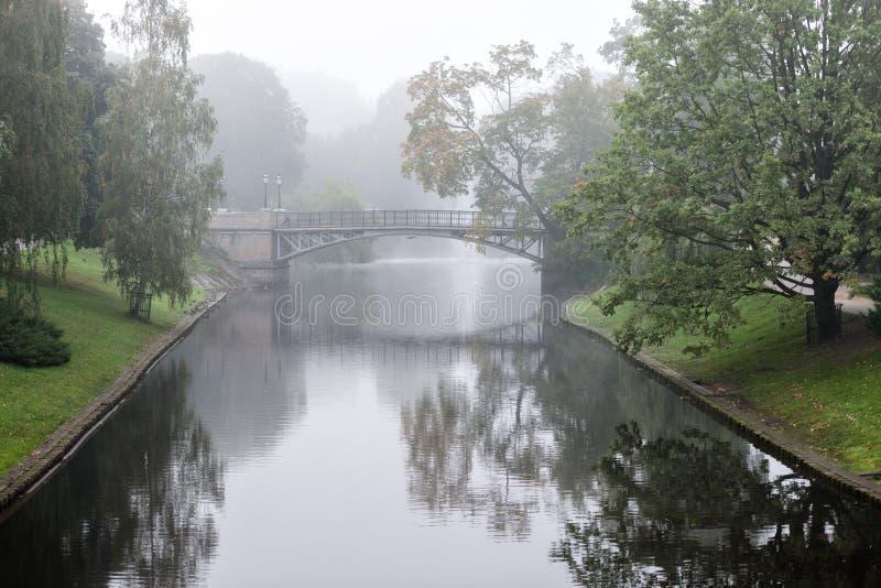 Πάρκο με ένα ομιχλώδες πρωί καναλιών Μέσω της ορατής γέφυρας υδρονέφωσης στοκ φωτογραφία