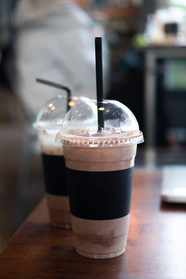 Πάρτε μαζί το φλυτζάνι του παγωμένου mocha καφέ και της παγωμένης σοκολάτας στον ξύλινο πίνακα στη καφετερία στοκ φωτογραφία
