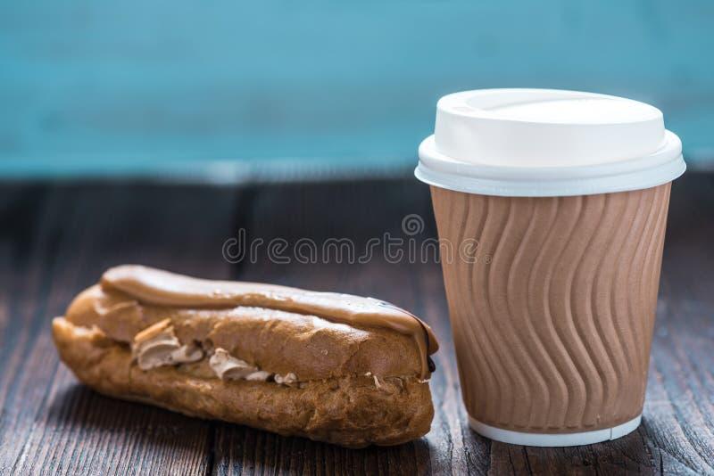 Πάρτε μαζί coffe με ECLAIR στο ξύλινο υπόβαθρο στοκ εικόνες με δικαίωμα ελεύθερης χρήσης