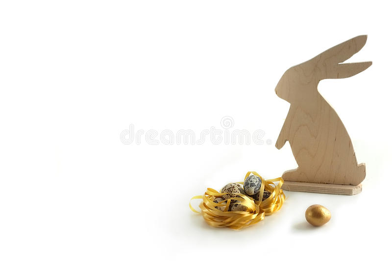 Πάσχα ευτυχές Ένα ξύλινο κουνέλι και αυγά ορτυκιών, ένα χρυσό αυγό Χρυσή φωλιά και χρυσό αυγό αυγά μικρά στοκ φωτογραφίες