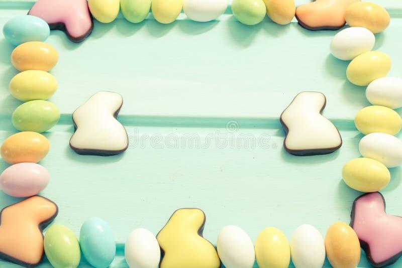 Πάσχα ευτυχές Γλυκά αυγά χρώματος κρητιδογραφιών και κουνέλια σοκολάτας στο υπόβαθρο μεντών Πλαίσιο Τοπ όψη Copyspace στοκ φωτογραφίες