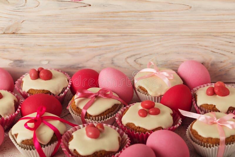 Πάσχα cupcakes με την άσπρη τήξη που διακοσμείται με τη ρόδινη καραμέλα και το ρ στοκ φωτογραφία με δικαίωμα ελεύθερης χρήσης
