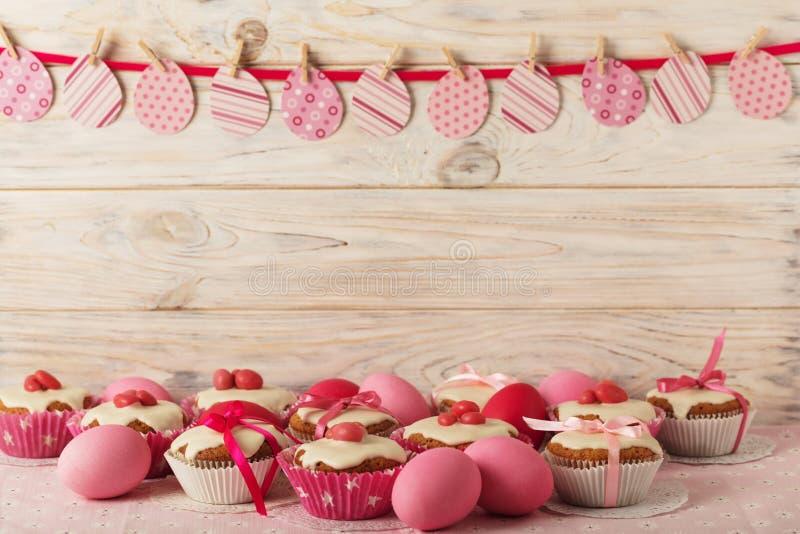 Πάσχα cupcakes με την άσπρη τήξη που διακοσμείται με τη ρόδινη καραμέλα και το ρ στοκ εικόνες