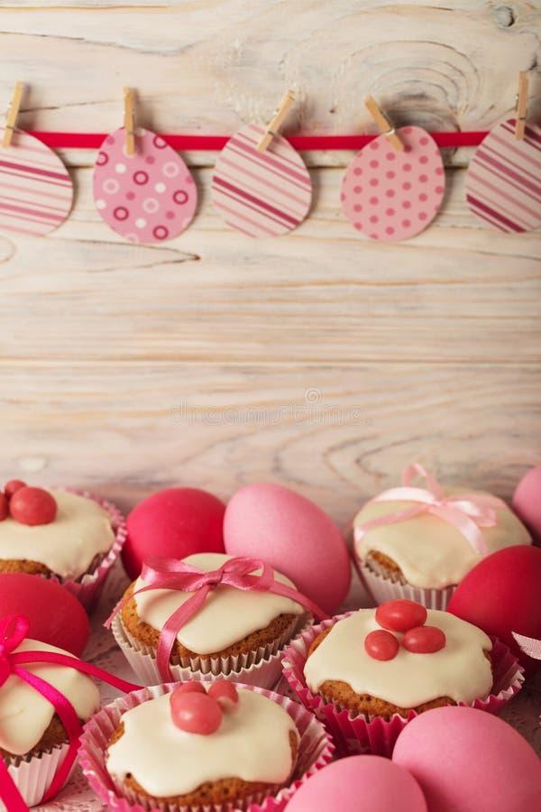 Πάσχα cupcakes με την άσπρη τήξη που διακοσμείται με τη ρόδινη καραμέλα και το ρ στοκ εικόνα