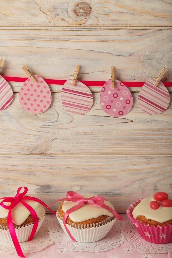 Πάσχα cupcakes με την άσπρη τήξη που διακοσμείται με τη ρόδινη καραμέλα και το ρ στοκ φωτογραφία