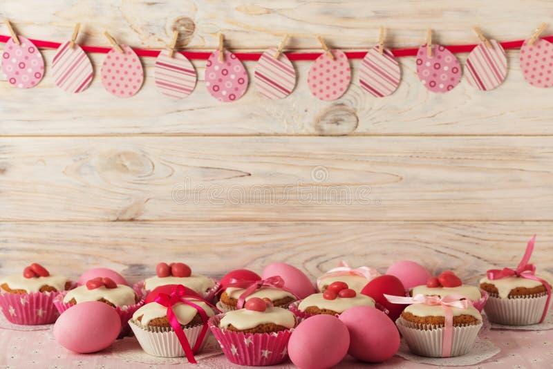 Πάσχα cupcakes με την άσπρη τήξη που διακοσμείται με τη ρόδινη καραμέλα και το ρ στοκ εικόνα με δικαίωμα ελεύθερης χρήσης