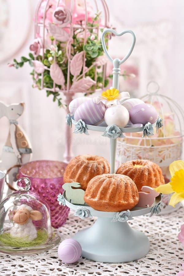 Πάσχα cupcakes στο μέταλλο cakestand στον εορταστικό πίνακα στοκ εικόνα με δικαίωμα ελεύθερης χρήσης