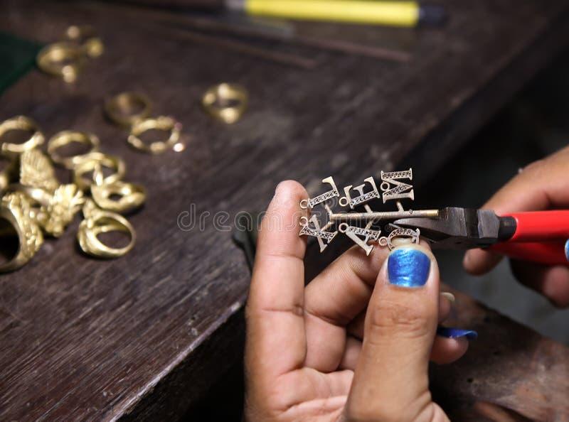 Πένσες χρήσης χρυσοχόων που κόβουν το σκουλαρίκι στοκ εικόνα με δικαίωμα ελεύθερης χρήσης