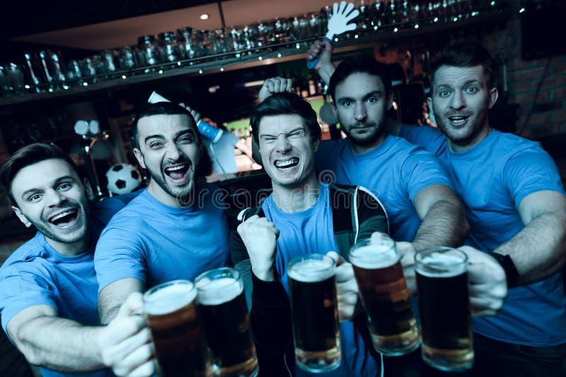 Πέντε αθλητικοί ανεμιστήρες που πίνουν την μπύρα που γιορτάζει και ενθαρρυντική μπροστά από τη TV στον αθλητικό φραγμό στοκ φωτογραφίες