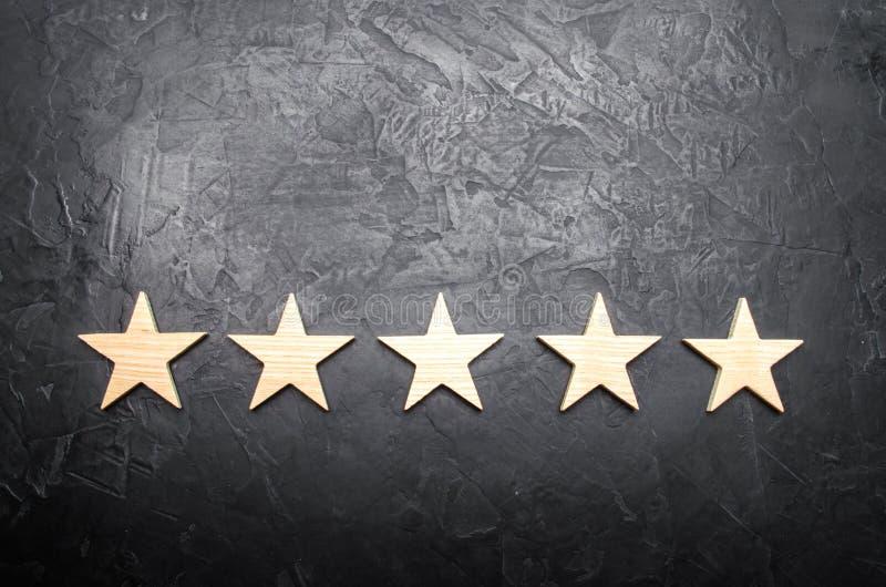 Πέντε αστέρια σε ένα σκοτεινό υπόβαθρο Η έννοια της εκτίμησης και της αξιολόγησης Η εκτίμηση του ξενοδοχείου, εστιατόριο, κινητή  απεικόνιση αποθεμάτων