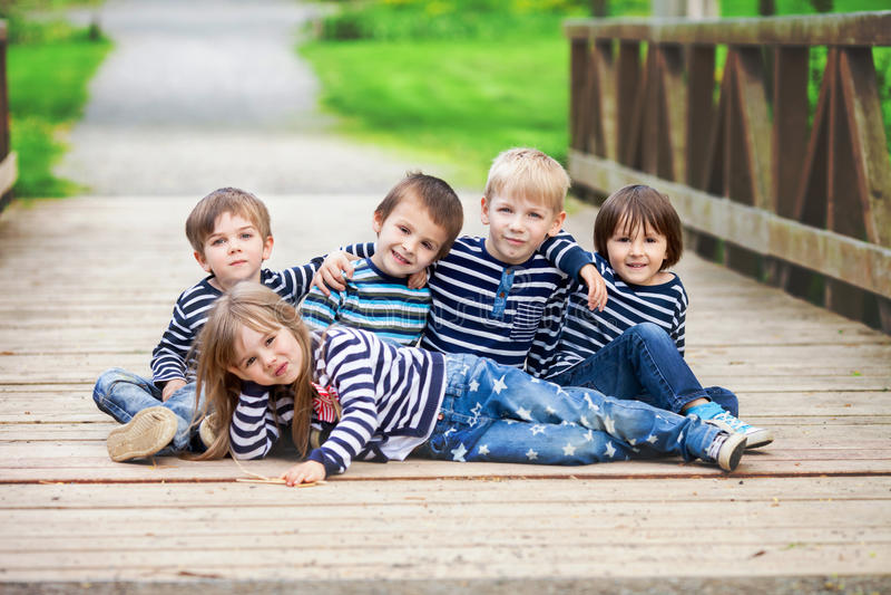 Πέντε λατρευτά παιδιά, έντυσαν στα ριγωτά πουκάμισα, το αγκάλιασμα και το smili στοκ εικόνα με δικαίωμα ελεύθερης χρήσης