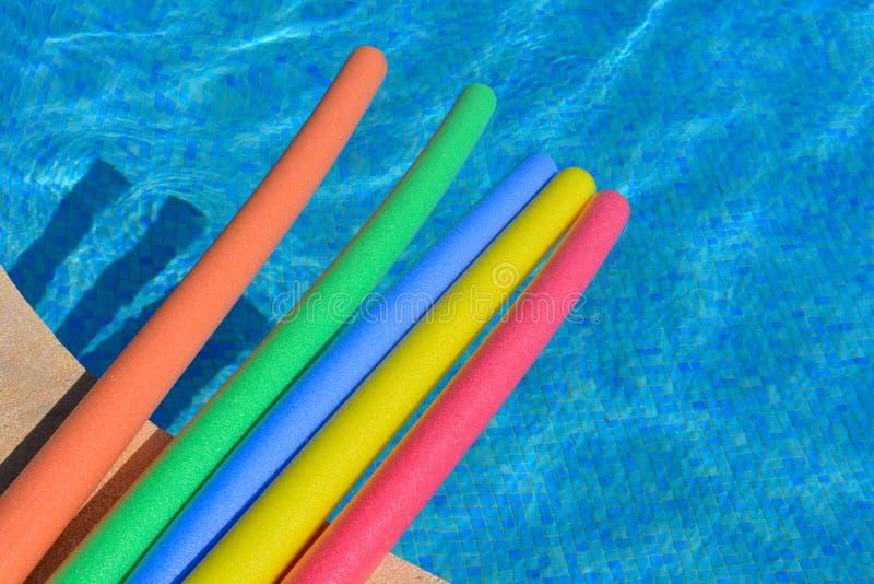 Πέντε δονούμενα, λαμπρά χρωματισμένα νουντλς λιμνών σε μια πισίνα, κανένας άνθρωπος στοκ φωτογραφία με δικαίωμα ελεύθερης χρήσης