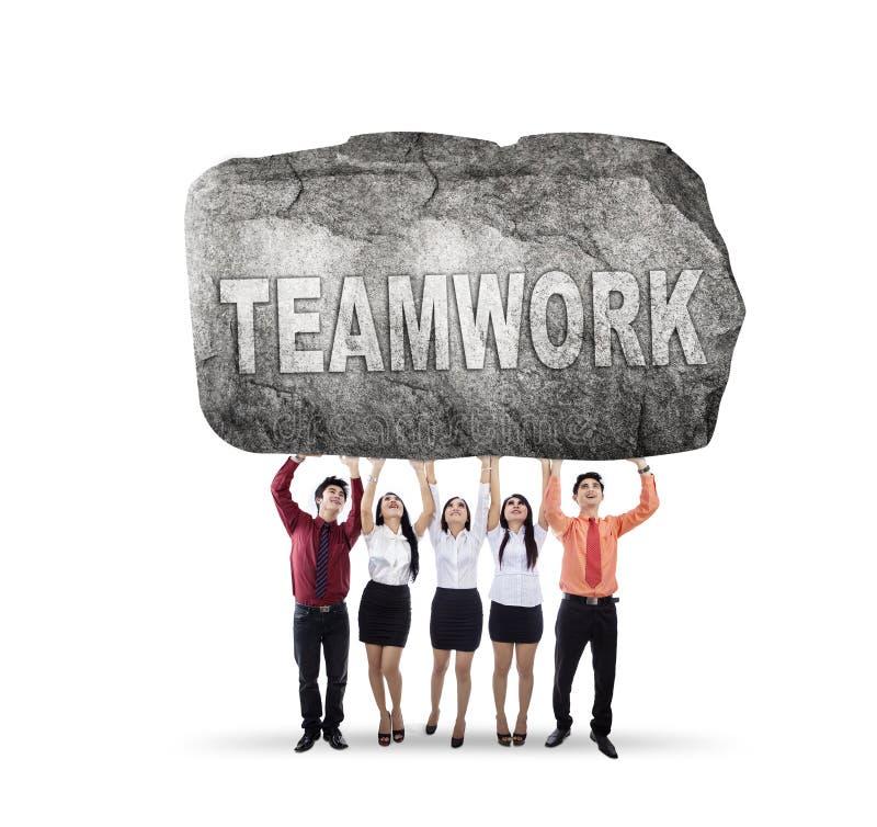 Πέντε επιχειρηματίες που ανυψώνουν τη λέξη ομαδικής εργασίας στοκ εικόνες