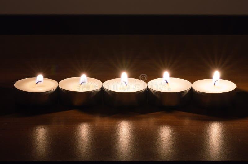 Πέντε κεριά κεριών σε ένα κάψιμο γραμμών στον ξύλινο πίνακα στοκ εικόνες