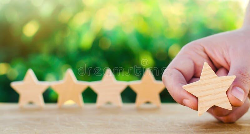 Πέντε ξύλινα αστέρια Πάρτε το πέμπτο αστέρι Η έννοια της εκτίμησης των ξενοδοχείων και των εστιατορίων, η αξιολόγηση των κριτικών στοκ φωτογραφία με δικαίωμα ελεύθερης χρήσης