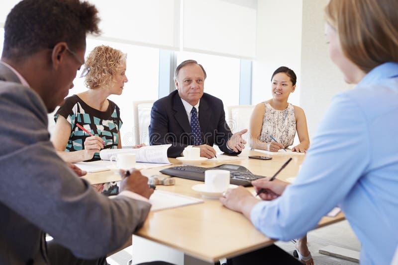 Πέντε Businesspeople που διοργανώνουν τη συνεδρίαση στην αίθουσα συνεδριάσεων στοκ εικόνα