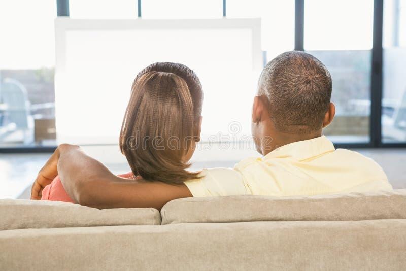 Πέρα από την άποψη ώμων του περιστασιακού ζεύγους που προσέχει τη TV στοκ εικόνα