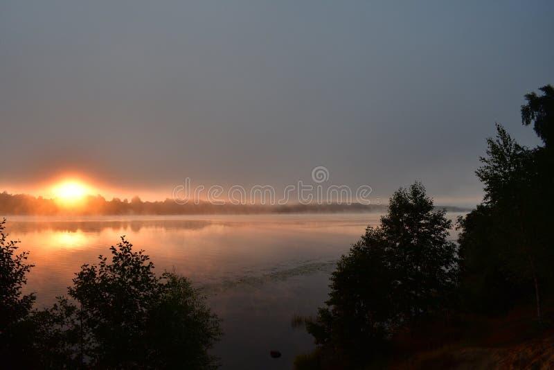 Πέρα από τον ποταμό η εμφάνιση του ήλιου από την ανατολή οριζόντων, αυγή, ομίχλη στοκ εικόνα
