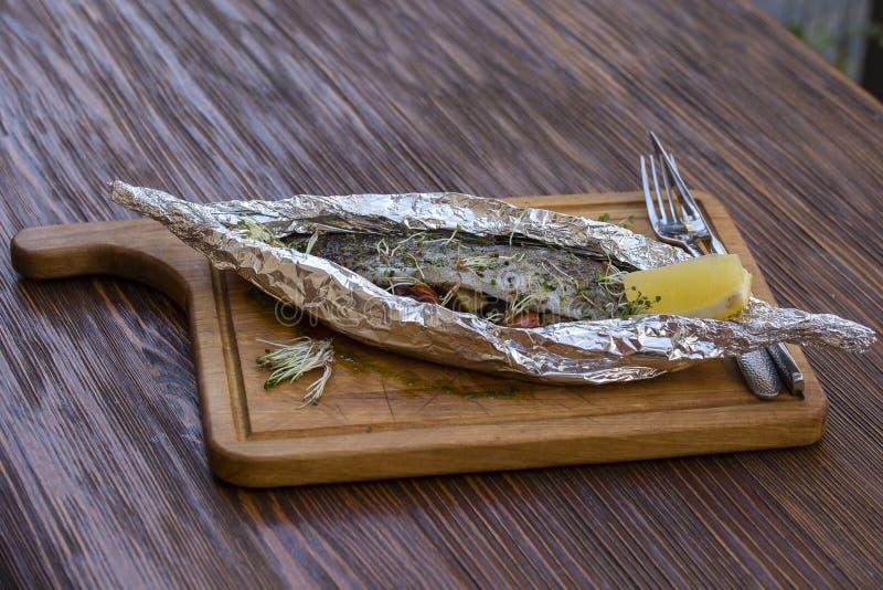 Πέστροφα που ψήνεται ολόκληρη με τα λαχανικά στο φύλλο αλουμινίου στον πίνακα στοκ φωτογραφία