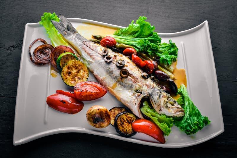 Πέστροφα ψαριών που ψήνεται με τα ψημένα στη σχάρα λαχανικά Σε μια ξύλινη ανασκόπηση στοκ εικόνα