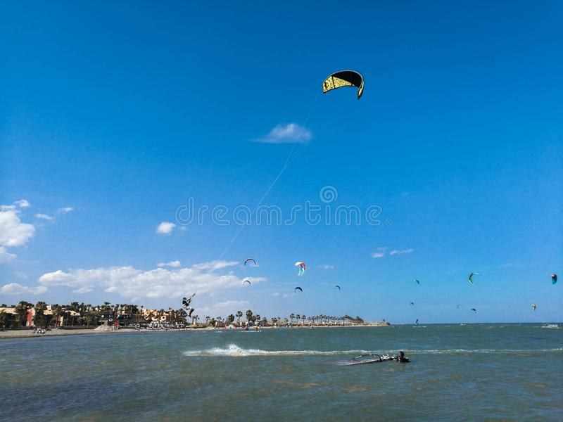 Πέταγμα αθλητικών τύπων τροφής ικτίνων υψηλό με τον ικτίνο και kiteboard στις μπότες στο μπλε ουρανό, τον ενεργό αθλητισμό και το στοκ εικόνα με δικαίωμα ελεύθερης χρήσης