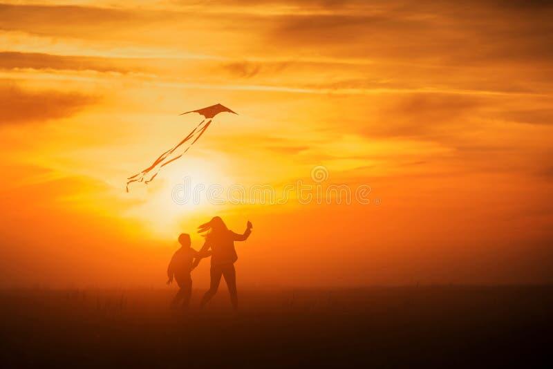 Πέταγμα ενός ικτίνου Το κορίτσι και το αγόρι πετούν έναν ικτίνο στον ατελείωτο τομέα Φωτεινό ηλιοβασίλεμα Σκιαγραφίες των ανθρώπω στοκ εικόνες
