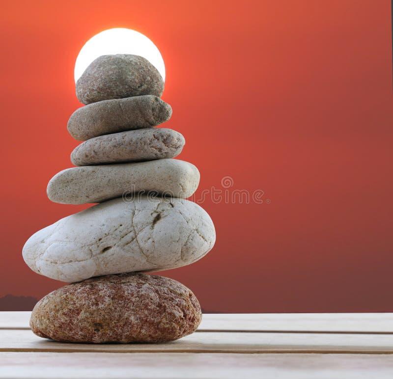 Πέτρες ισορροπίας που συσσωρεύονται στην πυραμίδα στο υπόβαθρο ηλιοβασιλέματος και το χ στοκ εικόνες