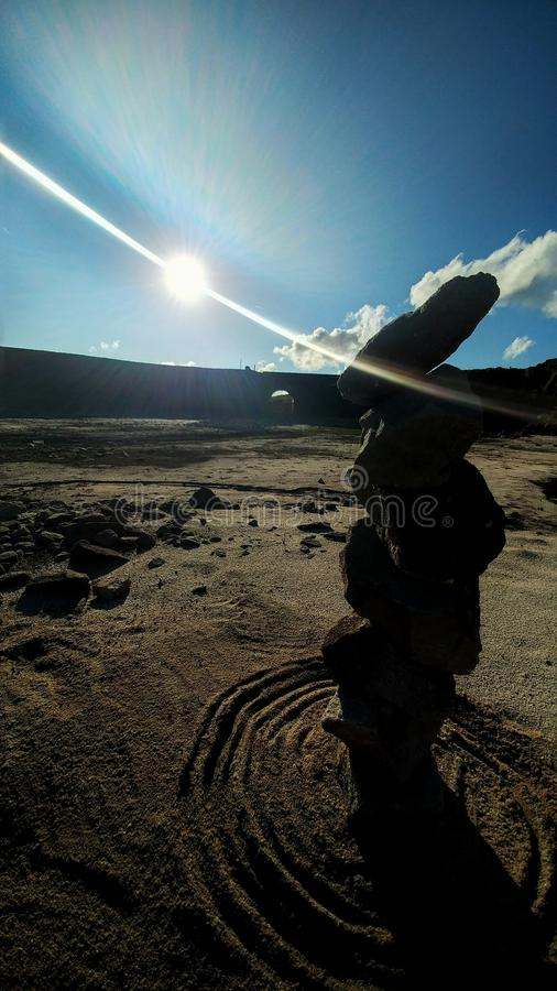 Πέτρες ισορροπίας στην άμμο και τον ήλιο στοκ εικόνες