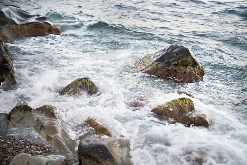 Πέτρες με το νερό και τον ψεκασμό, παφλασμός θάλασσα ακτών στοκ φωτογραφία