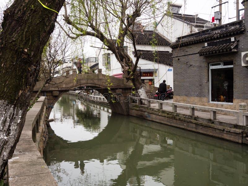 Πέτρινη γέφυρα που απεικονίζεται στα νερά καναλιών στην ιστορική παλαιά πόλη Suzhou στοκ φωτογραφίες