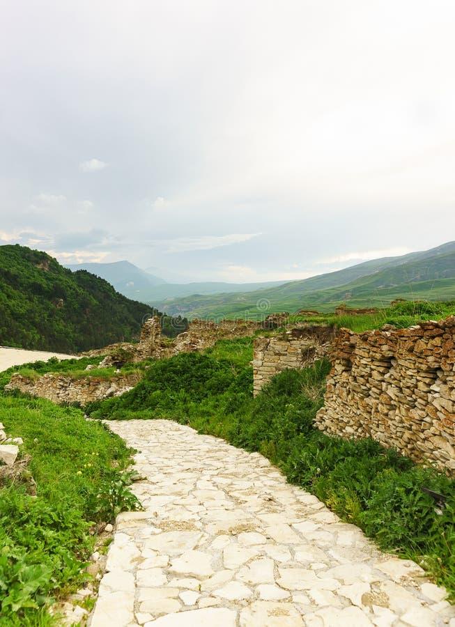 Πέτρινη πορεία στην αρχαία τακτοποίηση Hoi ενάντια στο σκηνικό των γραφικών βουνών του μεγαλύτερου Καύκασου Τεκτονική στοκ εικόνες