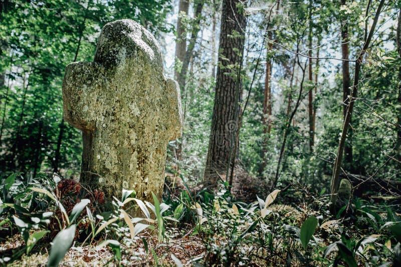 Πέτρινος σταυρός στο θερινό δάσος στο νεκροταφείο στοκ εικόνες