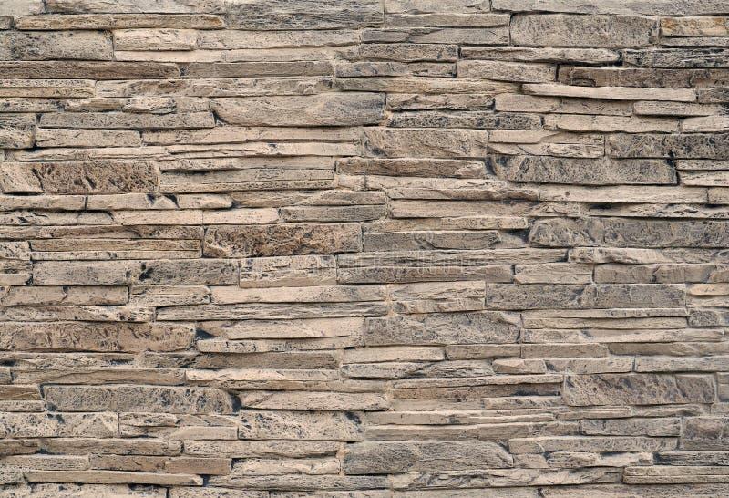 Πέτρινος τοίχος επένδυσης φιαγμένος από ριγωτές συσσωρευμένες πλάκες των φυσικών καφετιών βράχων που λεκιάζουν με το Μαύρο στοκ φωτογραφίες