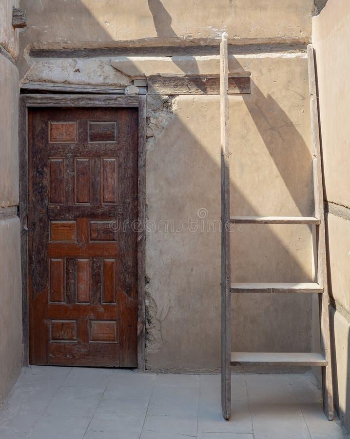 Πέτρινος τοίχος με την ξύλινη παλαιά διακοσμημένη πόρτα grunge και τη σπασμένη ξύλινη σκάλα στοκ εικόνες