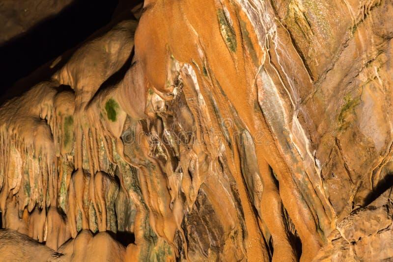 Πέτρινος τοίχος σε ένα υπόγειο grotto με έναν συνδυασμό καφετιών, κίτρινων και πράσινων χρωμάτων στοκ φωτογραφία με δικαίωμα ελεύθερης χρήσης