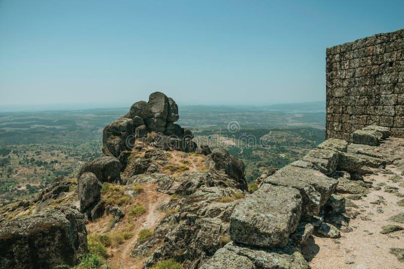 Πέτρινος τοίχος στην κορυφή υψώματος που καλύπτεται από τους βράχους στο Castle Monsanto στοκ εικόνα