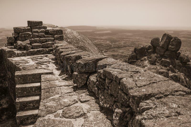 Πέτρινος τοίχος στην κορυφή υψώματος που καλύπτεται από τους βράχους στο Castle Monsanto στοκ εικόνα με δικαίωμα ελεύθερης χρήσης