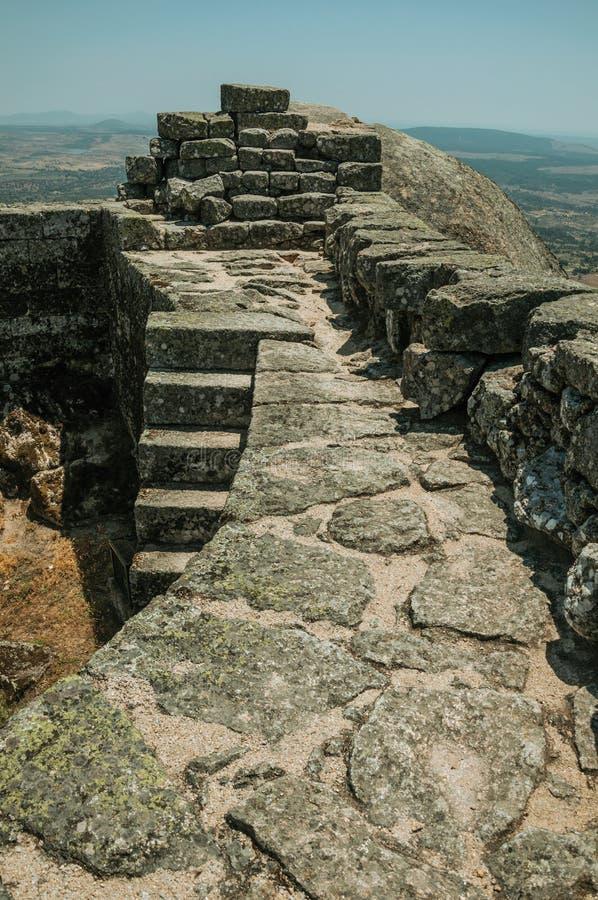 Πέτρινος τοίχος στην κορυφή υψώματος που καλύπτεται από τους βράχους στο Castle Monsanto στοκ εικόνες