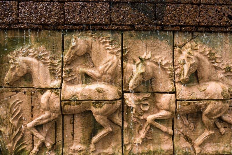 Πέτρινο γλυπτό του αλόγου στο τουβλότοιχο με τον καταρράκτη στοκ φωτογραφίες με δικαίωμα ελεύθερης χρήσης