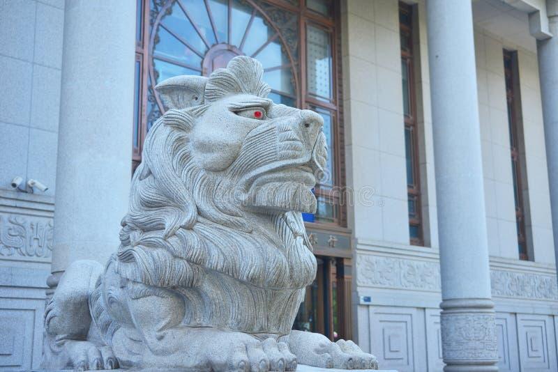 Πέτρινο λιοντάρι που στέκεται μπροστά από μια κινεζική τράπεζα στοκ εικόνες