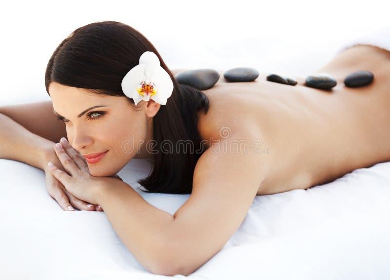 Πέτρινο μασάζ. Μασάζ Beautiful Woman Getting Spa καυτό πετρών. S στοκ εικόνες