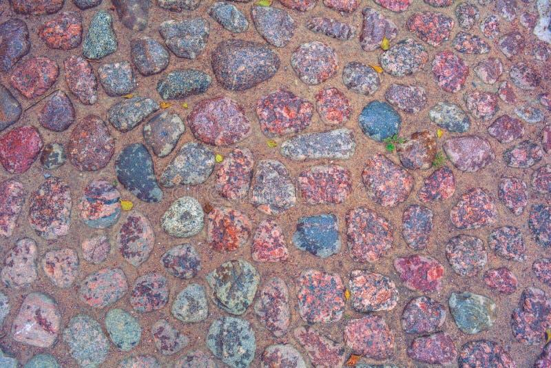 Πέτρινο πεζοδρόμιο με τους τραχιούς υγρούς λίθους γρανίτη Ιστορική μεσαιωνική cobble επίστρωση στοκ εικόνα