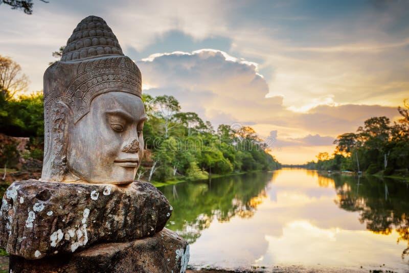 Πέτρινο πρόσωπο Asura και ηλιοβασίλεμα πέρα από την τάφρο angkor Καμπότζη thom στοκ εικόνες