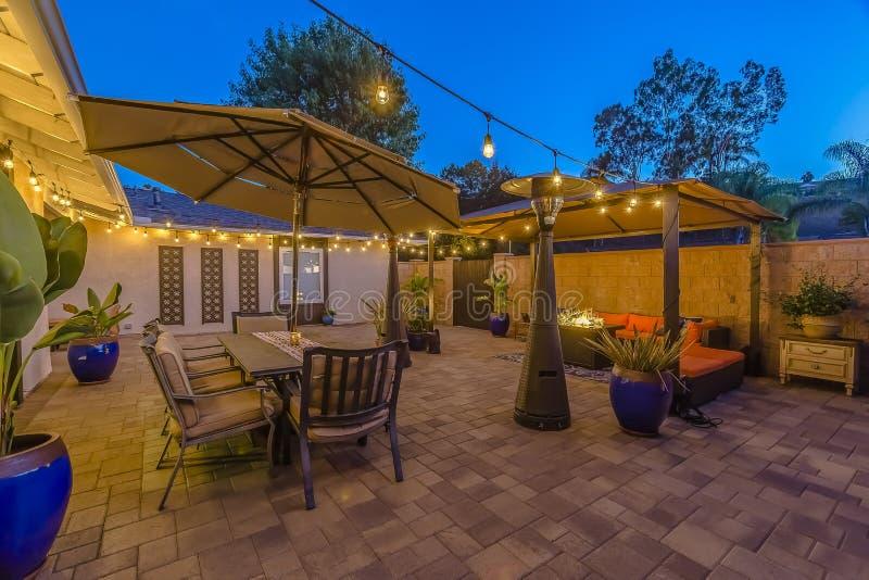 Πέτρινο patio με την περιοχή διατάξεων θέσεων κάτω από μια περιοχή gazebo και να δειπνήσει κάτω από μια ομπρέλα στοκ φωτογραφία με δικαίωμα ελεύθερης χρήσης