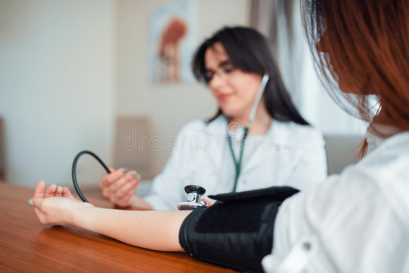 Πίεση σωμάτων μέτρων γιατρών μιας νέας μητέρας στοκ εικόνα με δικαίωμα ελεύθερης χρήσης